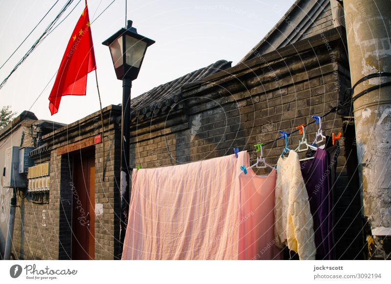 washday Far-off places Wall (building) Wall (barrier) Authentic Beautiful weather Street lighting Flag Cloudless sky Brick Hang Laundry Clothesline Chinese