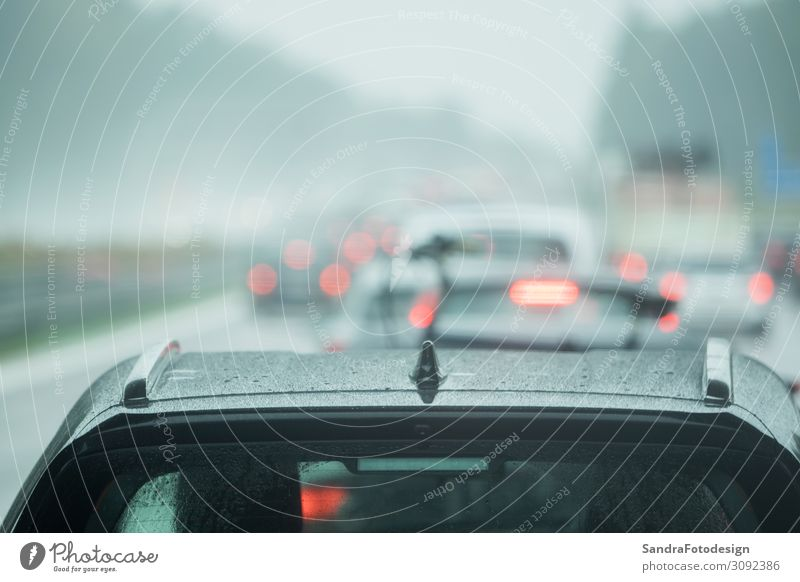 A car is driving on the road in the rain Vacation & Travel Environment Weather Bad weather Transport Motoring Street Highway Car Work and employment Wet