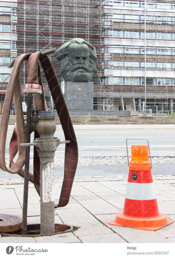 Hydrant with water hose and shut-off cone with warning light stands at the roadside, in the background the Karl-Marx monument in front of a house facade in Chemnitz