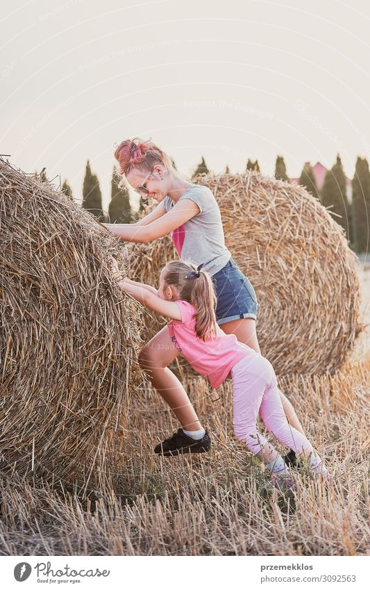 Sisters pushing hay bale playing together in the countryside Woman Child Human being Sky Vacation & Travel Nature Youth (Young adults) Young woman Summer Blue