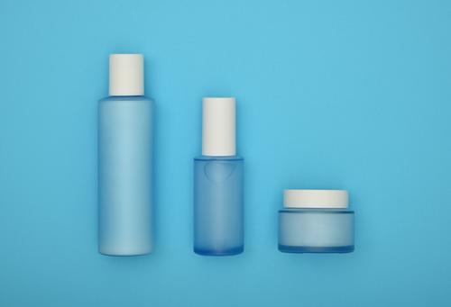 Set of cosmetic skin care cream bottles on blue Blue Beautiful White Face Feminine Health care Above Body Glass Skin Wellness Beauty Photography