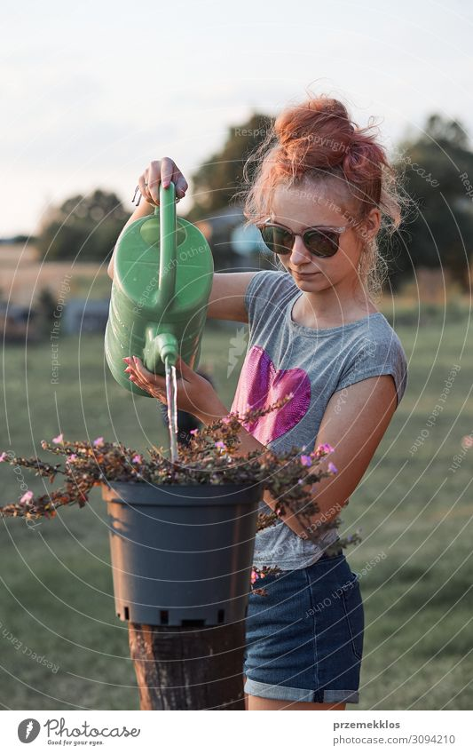 Teenage girl helping to water the flowers Pot Lifestyle Summer Garden Child Work and employment Gardening Human being Young woman Youth (Young adults) Woman