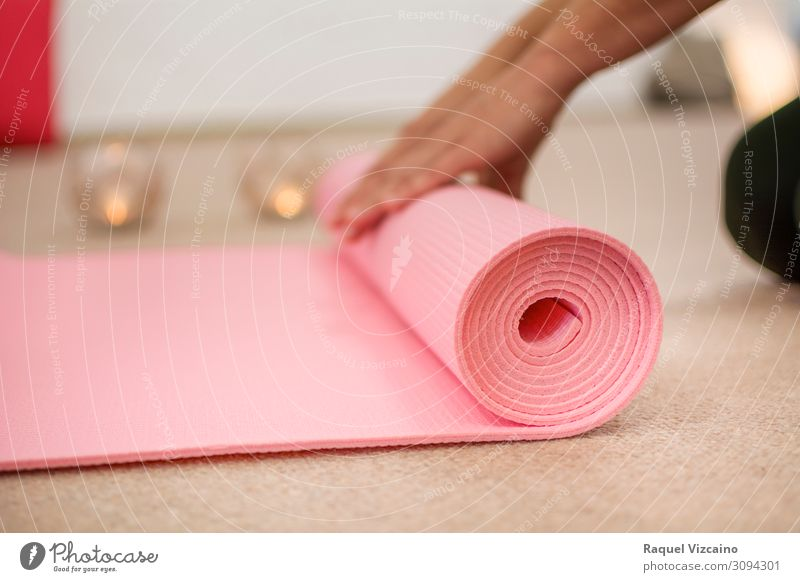 Woman hands winding the pink yoga mat. Lifestyle Wellness Relaxation Meditation Sports Yoga Hand Candle Breathe Healthy Brown Pink Peaceful Calm Contentment