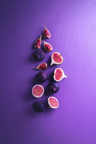 Fresh figs on a purple background. Sliced figs Vegetable Fruit Dessert Nutrition Vegetarian diet Diet Exotic Healthy Eating Delicious Juicy Violet Red