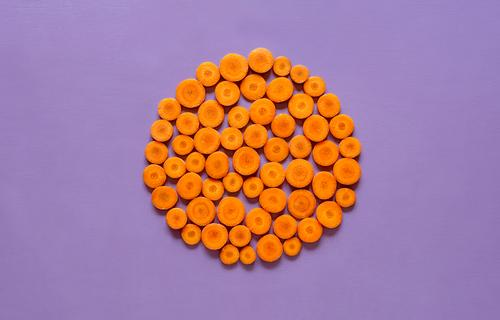 Sliced carrots in a circle on purple background Vegetable Nutrition Vegetarian diet Diet Healthy Eating Winter Autumn Fresh Natural Orange Arrangement Tradition