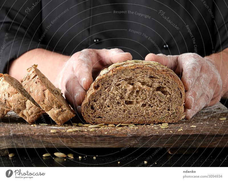 chef in black uniform keeps cut off a piece of bread Bread Nutrition Eating Lunch Dinner Table Kitchen Man Adults Hand Wood Dark Fresh Delicious Natural Brown