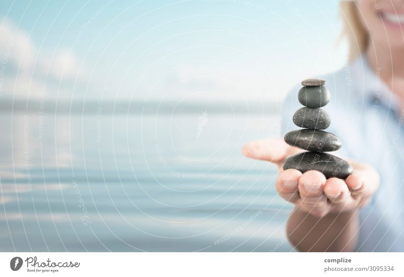 Keep Balance. A young woman is balancing a tower of stones. Healthy Alternative medicine Fitness Wellness Life Harmonious Well-being Relaxation Meditation Spa