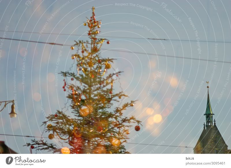 Kitschy, bizarre, decorated Christmas tree stands between wires, church, lamp and lantern in the city and lights up. Funny, abstract, bright, funny, urban Christmas mood with Christmas tree & light outside in front of blue sky in Advent