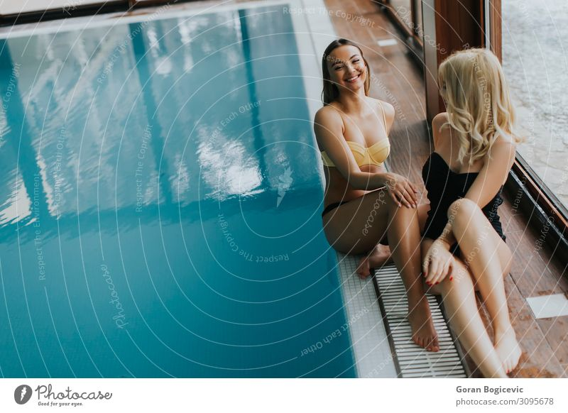 Attractive young women in bikini sits on the poolside Lifestyle Happy Beautiful Body Wellness Relaxation Swimming pool Leisure and hobbies Winter Human being