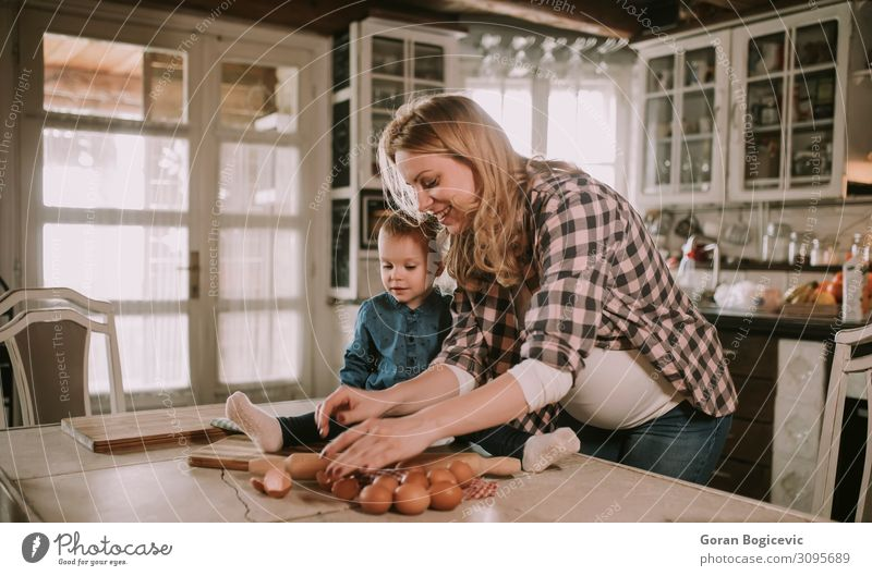 Pregnant woman and little daughter in the rustic kitchen Lifestyle Joy Happy Beautiful Table Kitchen Child Human being Girl Woman Adults Mother