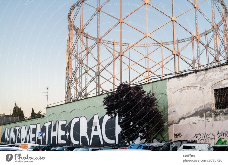 gasometer and mural graffiti Town Industrial plant Ruin Facade Graffiti Gasometer Rome Evening sun Society dilapidated Old Change motto Figure of speech