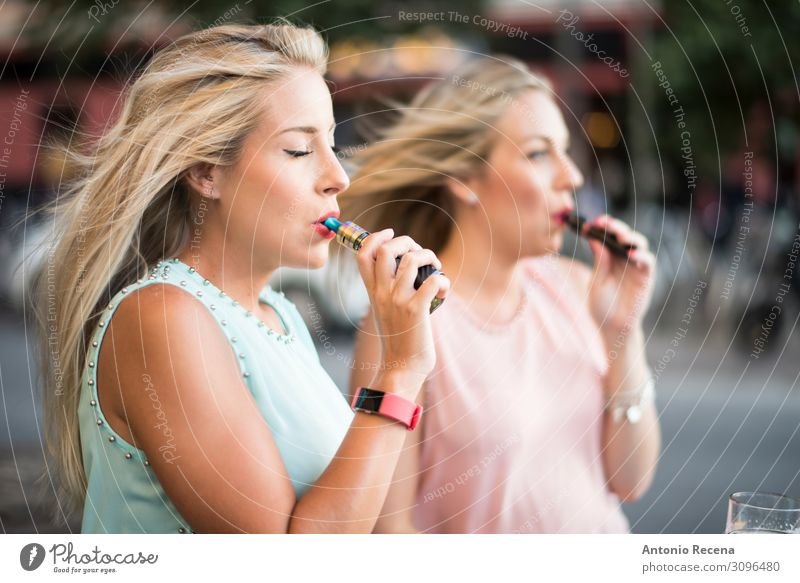 two blonde sister with e-cigar smoking in bar terrace Lifestyle Elegant Beautiful Leisure and hobbies Technology Human being Woman Adults Hand Street Fashion