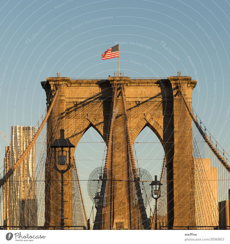 Brooklyn Bridge at sunrise Sunrise Sunset Sunlight Beautiful weather Town Skyline High-rise Tourist Attraction Landmark Blue Orange USA American Flag Lantern