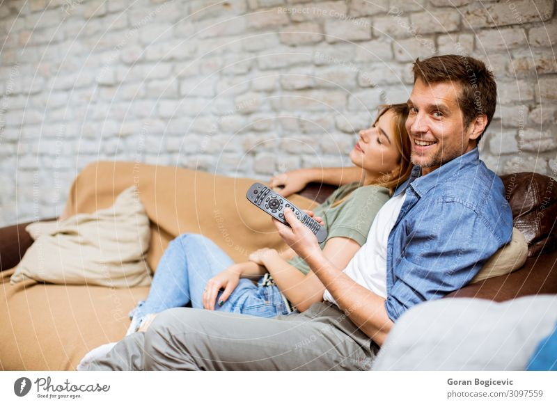 Smiling young couple relaxing and watching TV at home Lifestyle Joy Relaxation Flat (apartment) Sofa Technology Human being Woman Adults Man Family & Relations