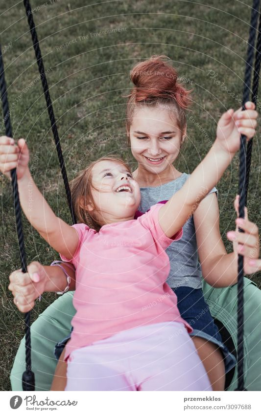 Sisters having fun on a swing together Joy Vacation & Travel Summer Summer vacation Garden Family & Relations Infancy 3 - 8 years Child 13 - 18 years
