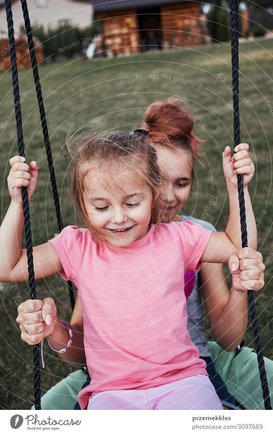 Sisters having fun on a swing together Joy Happy Summer Summer vacation Garden Child Family & Relations 2 Human being 3 - 8 years Infancy 13 - 18 years