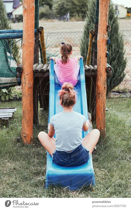 Sisters having fun on a slide together Lifestyle Joy Summer Summer vacation Garden Child Family & Relations 2 Human being 3 - 8 years Infancy 13 - 18 years