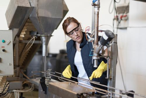 Worker woman revises machine in factory with protective glasses and gloves Bottle Work and employment Profession Factory Industry Human being Woman Adults Plant