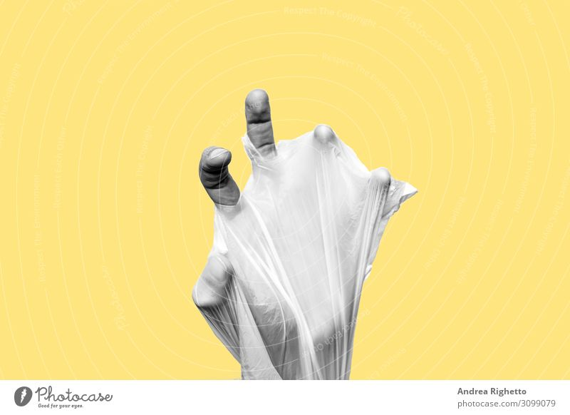 Concept of stop plastic pollution, global warming, recycling plastic, plastic free, zero plastic. Hand wrapped in a plastic bag. Yellow background with a black and white subject