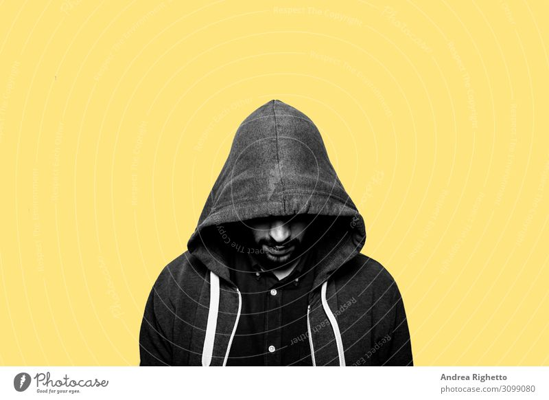 Concept of hacker, cyber threats, young depression, adolescence difficulties. Young caucasian male student staring at the floor with the eyes hide hided by a hood. Yellow background