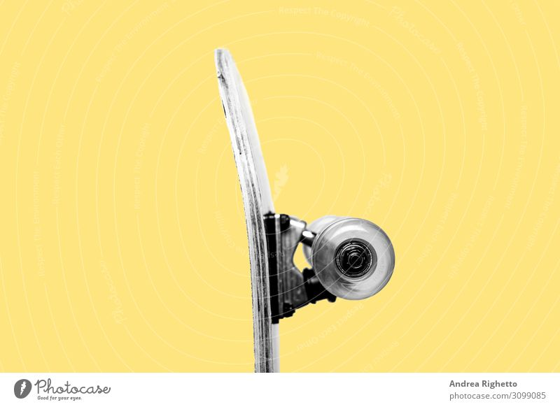 Concept of youth, indie culture, being a teenager, 90s nostalgic. Half of a profile of a skateboard in black and white at the center of image. Yellow background. Isolated