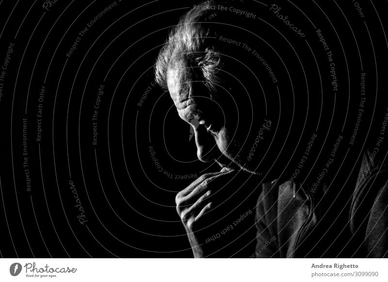 Concept of depression. Old man staring at nothing in the dark in black and white with a black background Health care Medical treatment Care of the elderly
