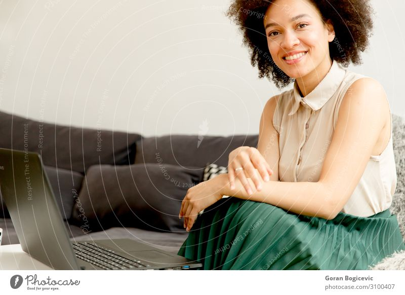 Young african american woman web-surfing internet Lifestyle Happy Beautiful Leisure and hobbies Sofa Computer Notebook Technology Telecommunications