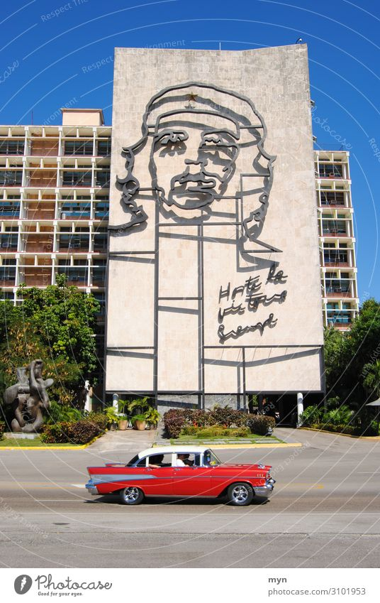 Portrait of Che Guevara on a house wall in Cuba with a vintage car in the foreground Vintage car che guevara portrait Havana Street Facade Wall (building)