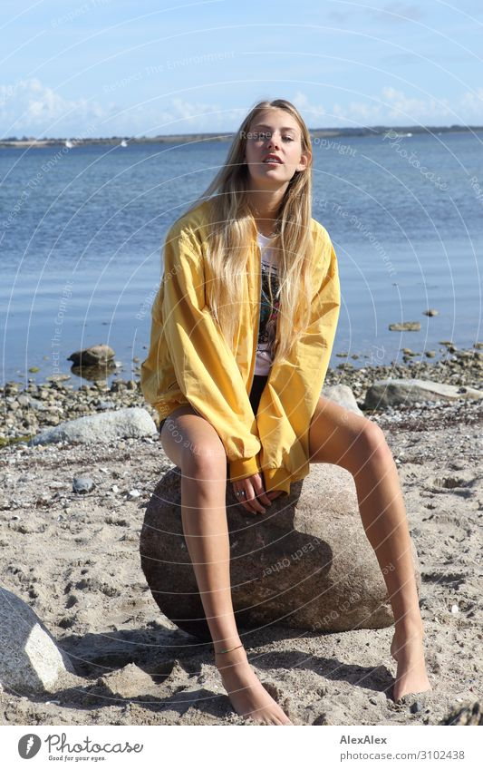 Young woman with yellow jacket sits on the beach Lifestyle Joy Beautiful Summer Sun Sunbathing Beach Ocean Youth (Young adults) Legs 18 - 30 years Adults