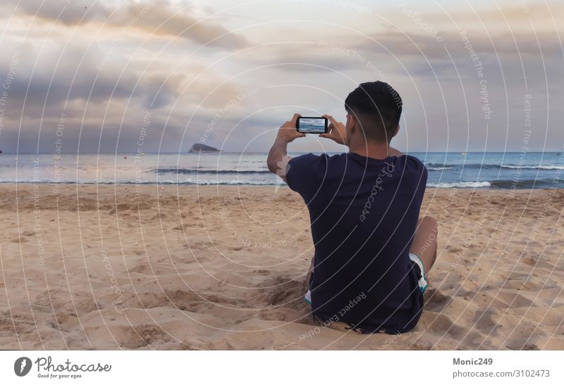 Boy facing the sea, taking a picture with a smartphone Happy Relaxation Vacation & Travel Tourism Beach Ocean Waves Telephone Cellphone Technology Internet