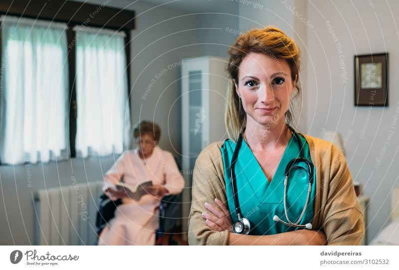 Pretty female doctor posing in a geriatric clinic Beautiful Health care Illness Relaxation Reading Bedroom Doctor Hospital Human being Woman Adults Old Smiling