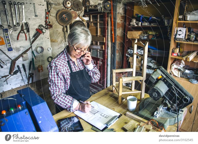 Female carpenter in her workshop Chair Craft (trade) Business To talk Human being Woman Adults Aircraft Wood Old Authentic carpentry Carpenter mobile senior