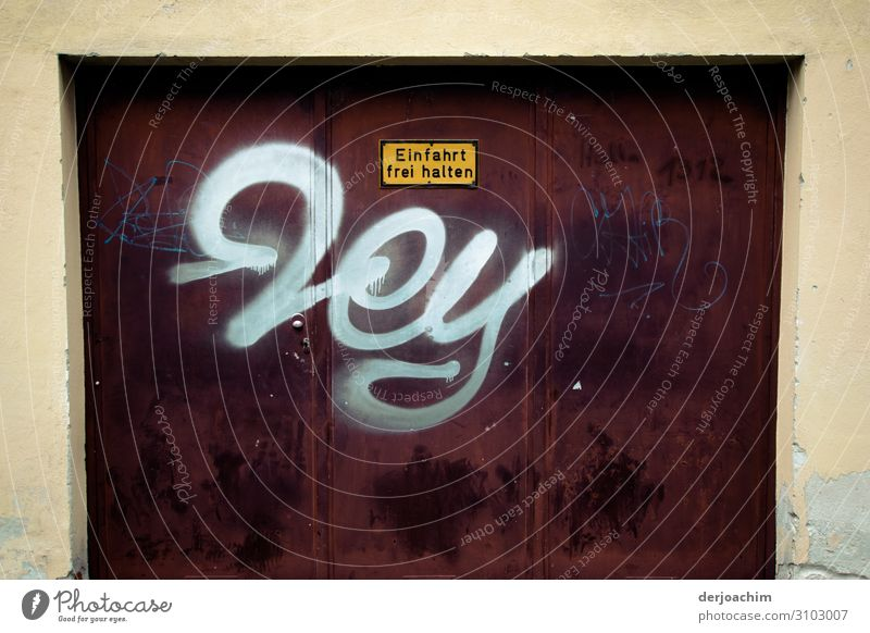 """""""Hey"""" is written on the garage door in white. Keep driveway clear. On dark background. Design Trip Garage Bavaria Germany Building Decoration Metal Characters"""