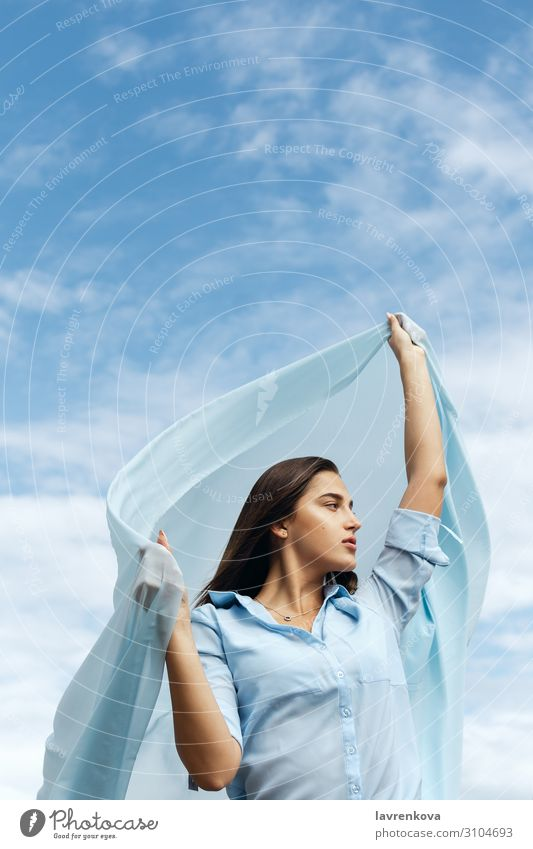 Young female holding cut of blue cloth up in the sky Adults Air Loneliness Attractive Blue Cloth Clouds Cut Woman Freedom Young woman Hand Happy Height Horizon