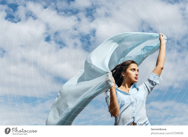 Young female holding cut of blue cloth up in the sky Air Horizon Height Exterior shot Attractive Summer Nature Happy Adults Loneliness Blue Cloth Clouds Cut
