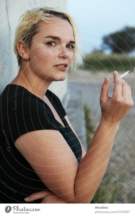 Young woman sitting on a block smoking a cigarette Style Beautiful Youth (Young adults) 18 - 30 years Adults Summer Beautiful weather T-shirt Piercing Blonde
