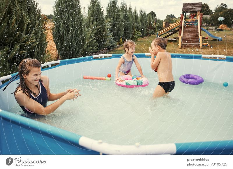 Children splashing in a pool Lifestyle Joy Happy Relaxation Swimming pool Playing Vacation & Travel Summer Garden Human being Girl Boy (child)