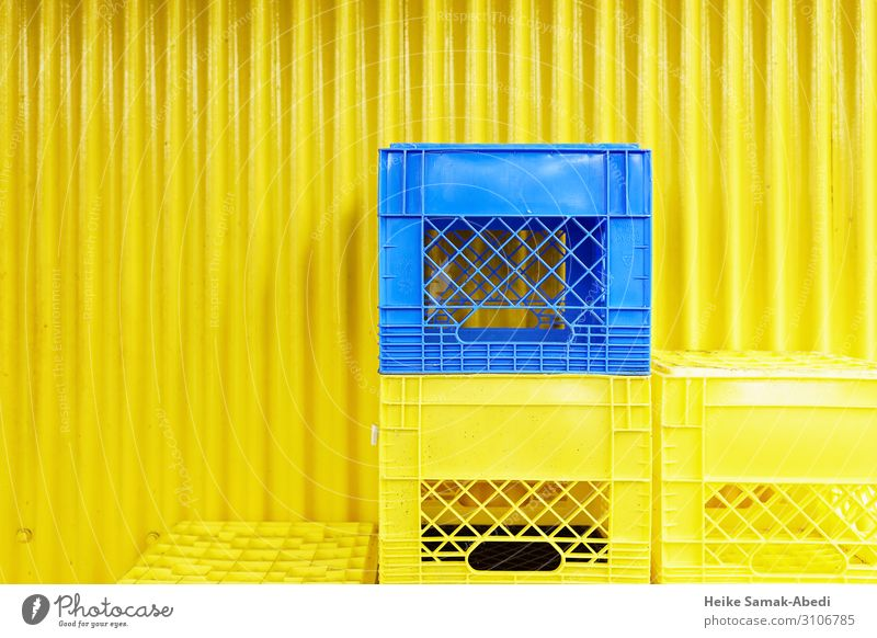 Yellow and blue boxes in front of a yellow corrugated iron wall Shopping Wall (barrier) Wall (building) Facade Box Plastic Blue Containers and vessels Stack