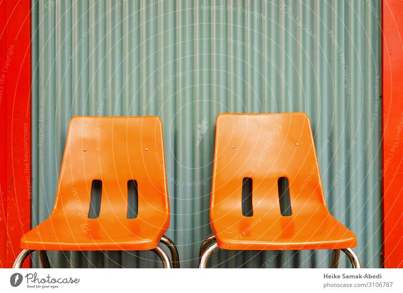 Orange-coloured chairs in front of a corrugated sheet metal wall Interior design Furniture Chair Wall (barrier) Wall (building) Facade Sit Break Calm Relaxation