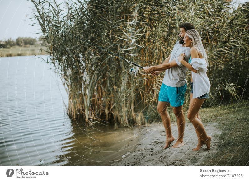Young couple enjoying fishing on sunny day at a calm lake Lifestyle Happy Beautiful Relaxation Leisure and hobbies Camping Summer Sun Entertainment Woman Adults