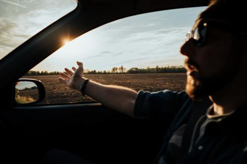 man in driving car with arms out of the window adventure auto caucasian countryside day drive field hands journey lifestyle male men passenger person ride road