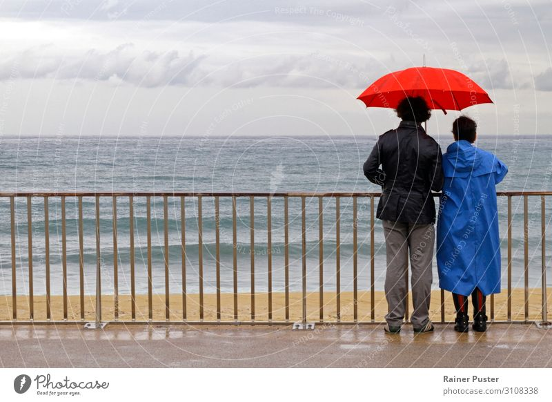 Couple with umbrella on the coast near Barcelona Human being 45 - 60 years Adults Clouds Autumn Bad weather Rain Beach Umbrellas & Shades Looking Wait Together