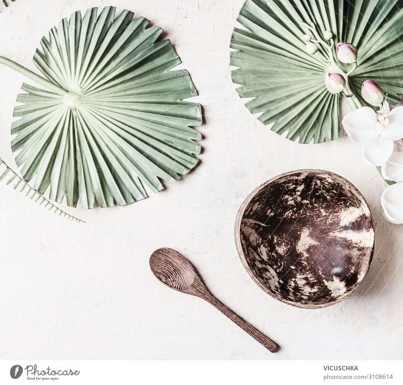 Empty coconut bowl with spoon on white desk background with tropical leaves, top view. Copy space for your design or product empty copy creative above style