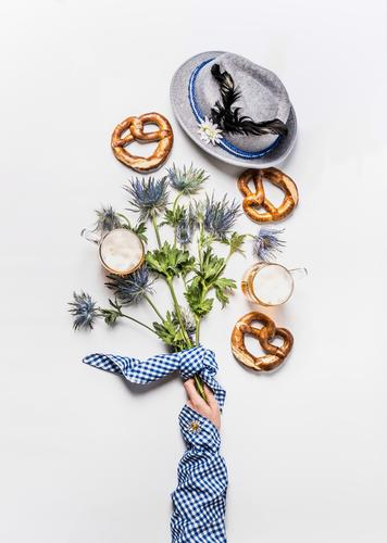 Maß beer, Bavarian hat with feather, pretzel and female hand Beverage Cold drink Beer Design Joy Table Party Event Restaurant Oktoberfest Woman Adults Hand