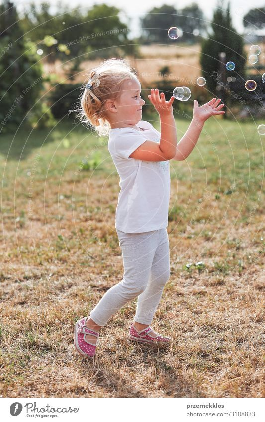 Little gir playing with soap bubbles Lifestyle Joy Happy Playing Garden Child Girl Infancy 1 Human being 30 - 45 years Adults Playground To enjoy Authentic