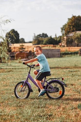 Happy smiling boy riding a bike Lifestyle Joy Relaxation Leisure and hobbies Playing Summer Garden Child School Human being Boy (child) Infancy 1 30 - 45 years
