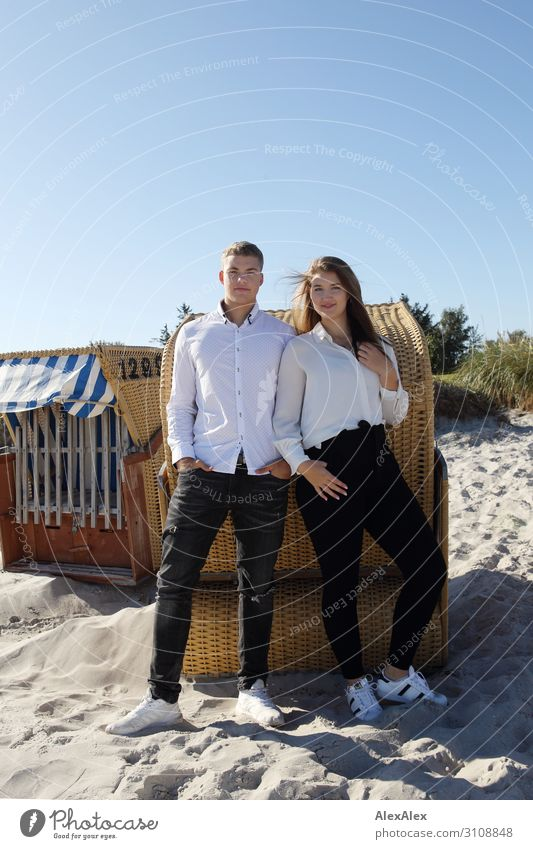 Young man and young woman on the beach in front of a beach chair Joy already Harmonious Summer Summer vacation Sun Beach Young woman Youth (Young adults)