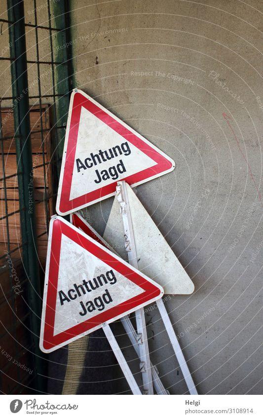 "several warning signs with the inscription ""Achtung Jagd"" are placed on a wall Wall (barrier) Wall (building) Metal Characters Signage Warning sign Stand"
