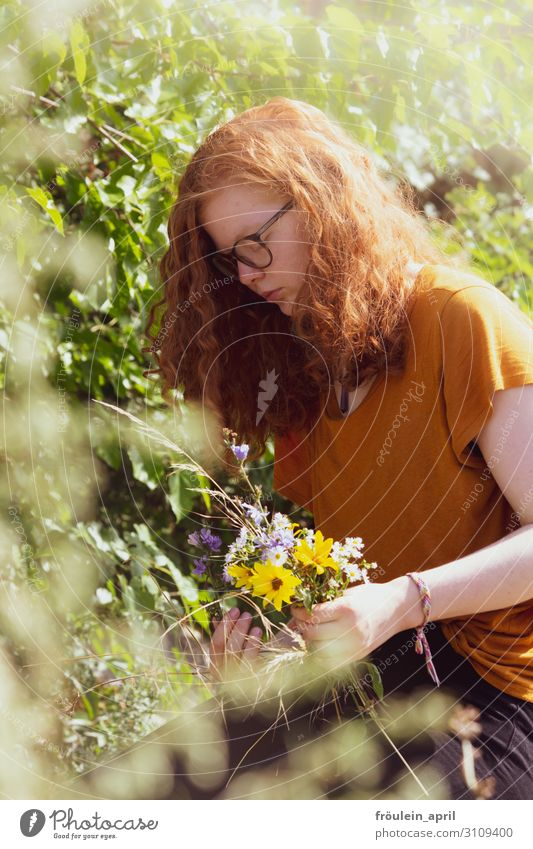 redheaded young woman tying a bouquet of wild flowers Bouquet Eyeglasses Portrait format Summer Sunflowers daylight Red-haired Human being Feminine Colour photo
