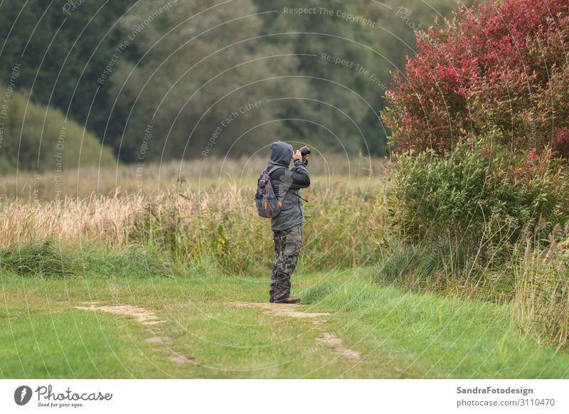 A man photographs something and stands in a meadow Lifestyle Joy Leisure and hobbies Vacation & Travel Summer Hiking Sports Human being 1 Artist Nature